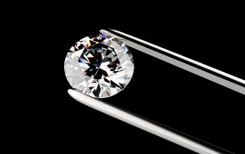 Diamond in the tweezers on a black background